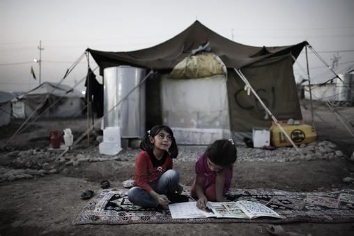 Iraq, 2013: Violence and forced flight have taken a toll on children's education – leaving nearly 3 million children in the Syrian Arab Republic and neighbouring countries out of school. Girls complete homework outside their tent home in Kawergosk refugee camp. In March 2014, the Syrian Arab Republic marks a tragic milestone as it concludes a third year of conflict. Another year of violence could be the point of no return for the millions of young Syrians at risk of becoming a lost generation | Credit: UNICEF