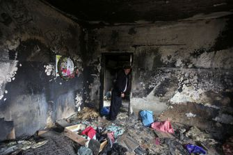 Terrorist Victims: A relative stands inside the burnt-out home of Saad Dawabsha, who was killed alongside his infant and wife when Jewish extremists firebombed their house in the West Bank village of Duma last July. - Getty Images