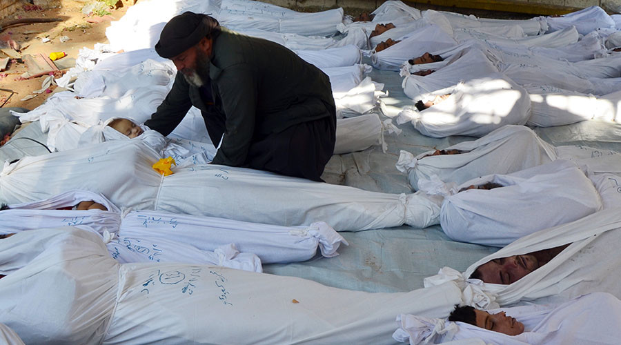 A man holds the body of a dead child among bodies of people activists say were killed by nerve gas in the Ghouta region, in the Duma neighbourhood of Damascus August 21, 2013. © Bassam Khabieh / Reuters