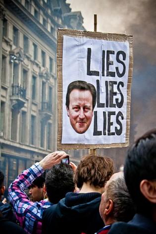 A plaque targeting Prime Minister David Cameron, as demonstrators protest in Oxford Street, London, 26 March 2011. Credit: Mark Ramsay | Source: http://www.flickr.com/photos/neutronboy/5562337245/ | Creative Commons Attribution 2.0 Generic license