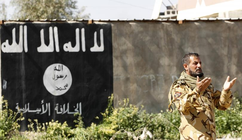 A member of a group of militias known as Hashid Shaabi prays as he celebrates victory next to a wall painted with the black flag commonly used by ISIS militants, in the town of al-Alam, Iraq, March 10, 2015. Photo: Reuters/Thaier Al-Sudani