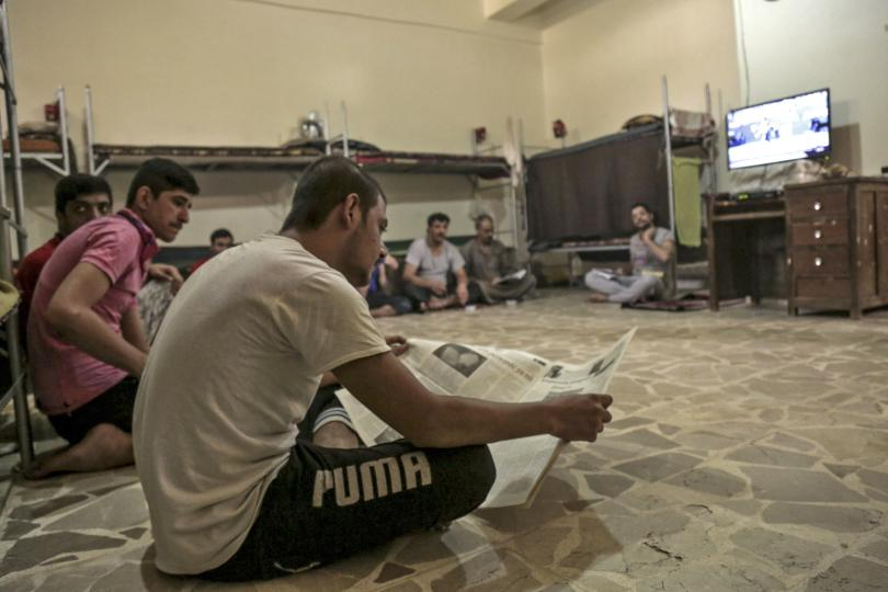 Prisoners watch television as one of them reads a newspaper inside Derick central prison, east of Syrian Kurdish city of Qamishli, Syria, Sept. 10, 2015. Photo: Reuters/Rodi Said