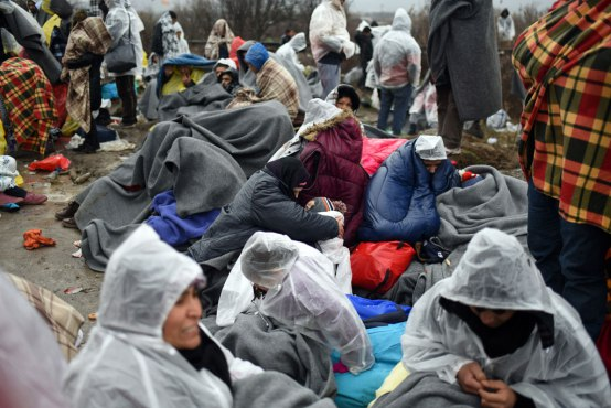 Afghanistan refugees sit huddled under blankets in very cold, wet weather conditions as they wait for permission to cross the border to Serbia from the Tabanovce in the former Yugoslav Republic of Macedonia, where border changes in the Balkan region have created confusion and chaos. Photo: UNICEF/UN010680/Georgiev