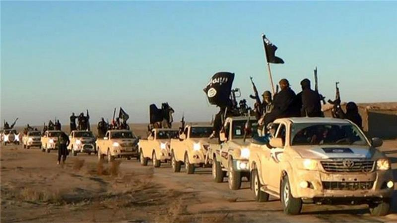 ISIL fighters on a road leading to Iraq, in Raqqa, Syria [AP]