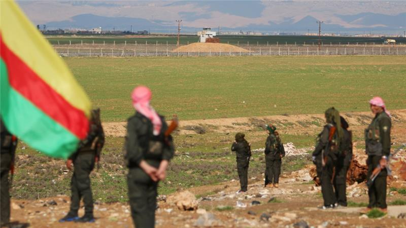 Kurdish fighters stand near the Syrian-Turkish border during a protest against Turkish operations against the Kurds [REUTERS]
