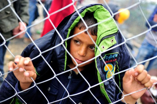 A boy clutches and looks through a chain-link fence, on a rainy day near the Former Yugoslav Republic of Macedonia town of Gevgelija, on the border with Greece. September 2015 Photo: UNICEF/UNI196199/Georgia