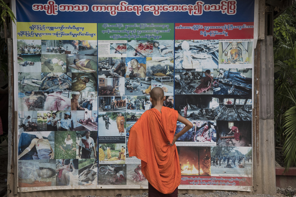 MANDALAY, MANDALAY REGION, MYANMAR - 2015/05/24: A young Buddhist novice looks at a panel filled with pictures showing atrocities allegedly committed by Muslims against Buddhists. This panel is erected in front of Buddhist monk Wirathu's quarters at Ma Soe Yein monastery (Mandalay). Wirathu is considered as a leader of a Myanmar radical Buddhist nationalist movement professing strong anti-Muslim propaganda. (Photo by Thierry Falise/LightRocket via Getty Images)