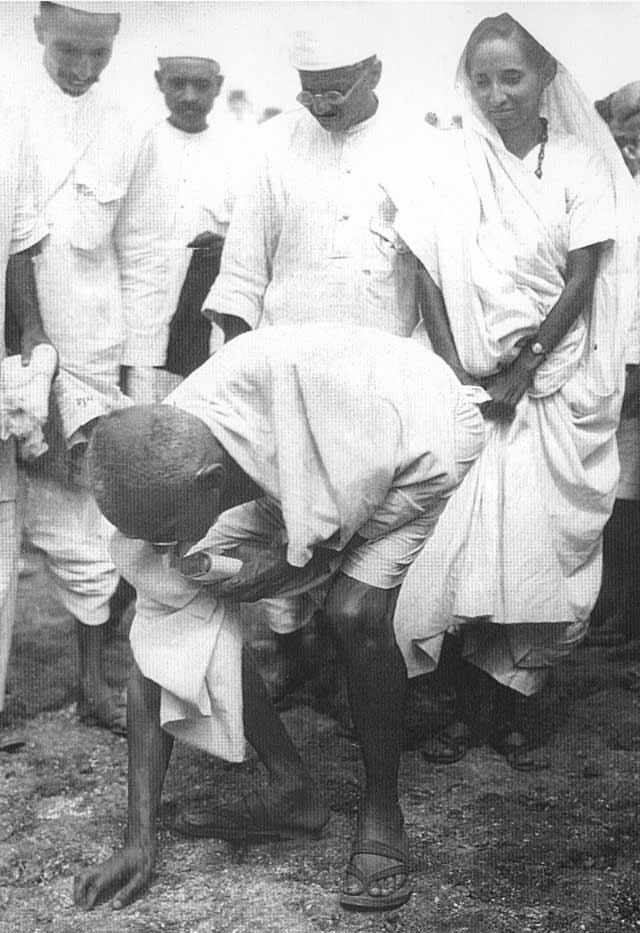 Gandhi recogiendo granos de sal al final de su marcha.  en.wikipedia.org