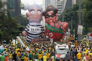 """Demonstrators parade large inflatable dolls depicting Brazil's former President Lula da Silva in prison garb and current President Rousseff dressed as a thief, with a sash that reads """"impeachment,"""" in São Paulo, Brazil, March 13, 2016. Photo: Andre Penner/AP"""