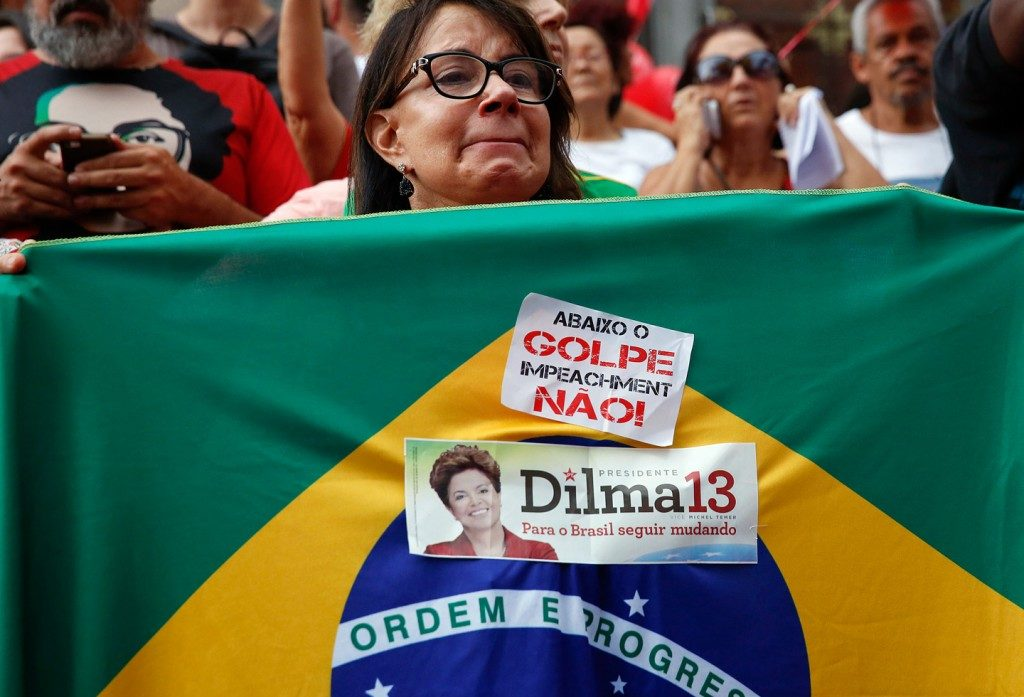 """Uma manifestante carrega uma bandeira brasileira com um cartaz onde se lê """"Abaixo o GOLPE impeachment NÃO!"""" durante um protesto em apoio à presidenta do Brasil Dilma Rousseff e o ex-Presidente Luiz Inácio Lula da Silva, em São Paulo, Brasil, 31 de março de 2016 . Foto: Andre Penner / AP"""