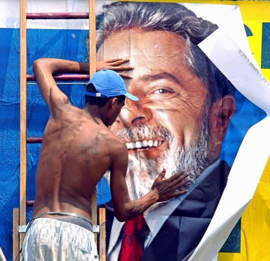 Um trabalhador cola um cartaz para a campanha do candidato presidencial Luiz Inácio Lula da Silva, do Partido dos Trabalhadores (PT). 24 de outubro de 2002, em São Paulo, Brasil. Foto: Mauricio Lima / AFP / Getty Images