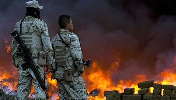 Two soldiers watch 134 tonnes of marijuana burning in the border town of Tijuana, Mexico. | Photo: AFP