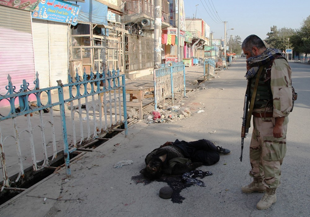 Afghan security forces walk past a Taliban fighter's dead body after retaking Kunduz from the Taliban, Oct. 4, 2015. Photo: Jawed Dehsabzi/Anadolu Agency/Getty Images