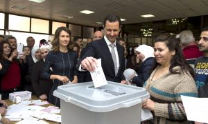 Syria's President Bashar al-Assad (C) casts his vote next to his wife Asma (centre left) inside a polling station during parliamentary elections in Damascus, Syria, on April 13, 2016.