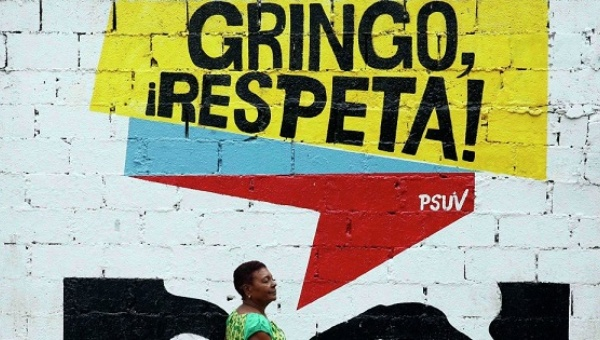 "A woman walks by a sign of the United Socialist Party in Venezuela that reads: ""Gringo Respect!"". 