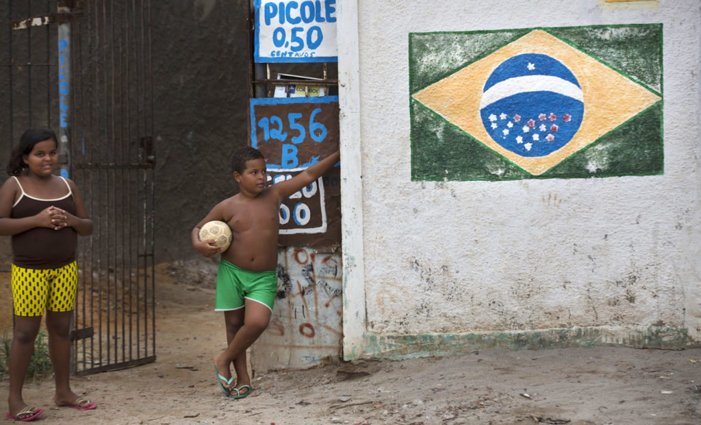 Children stand outside a small store in Olinda, Brazil, on Jan. 20, 2016. Photo: Rafael Fabres/Bloomberg/Getty Images