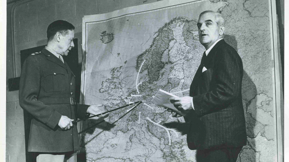 US Army General Allen Gullion and Fred K. Hoehler, Director of the United Nation's Division of Displaced Persons, stand before a map predicting the movement of European refugees of World War II. Many Europeans would find a haven in refugee camps in the Middle East. Credit: Courtesy of the Fred K. Hoehler Papers in the Social Welfare History Archives, University of Minnesota