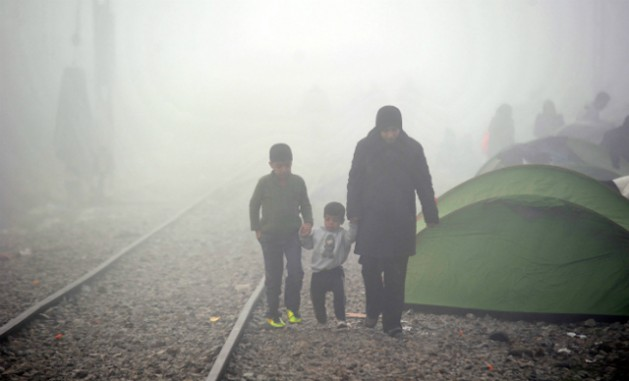 In March 2016, a mother walks though misty weather with her two sons along train tracks in Idomeni, Greece. Credit: ©UNICEF/UN012794/Georgie