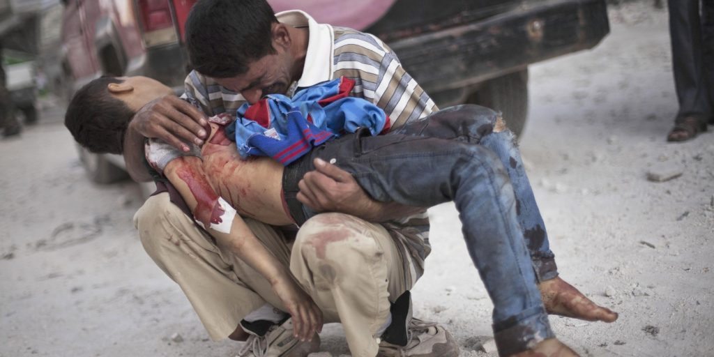 A Syrian man holds the body of his son, killed by the Syrian Army, near Dar El Shifa hospital in Aleppo on Oct. 3, 2012.