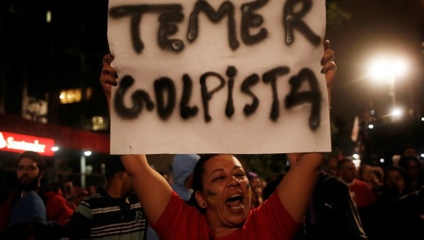 """A protester holds a sign that reads """"Temer coup-monger,"""" after the Brazilian Senate voted to suspend President Dilma Rousseff, Sao Paulo, Brazil, May 12, 2016. 