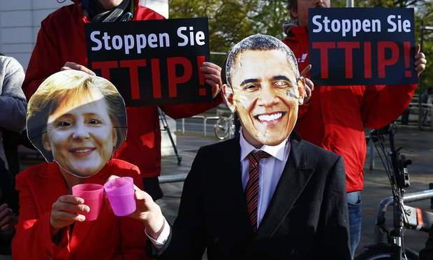 Protesters wear masks of Barack Obama and Angela Merkel as they demonstrate against TTIP free trade agreement. Photograph: Wolfgang Rattay/Reuters