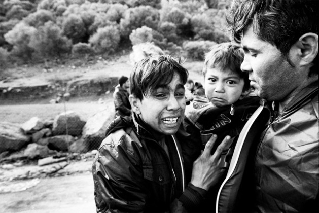 With fear etched on their faces, clearly still suffering from the trauma of a rough by boat across the Aegean, an Afghan family arrives in Lesvos, Greece (2015). Photo credit: UNHCR/Giles Duley