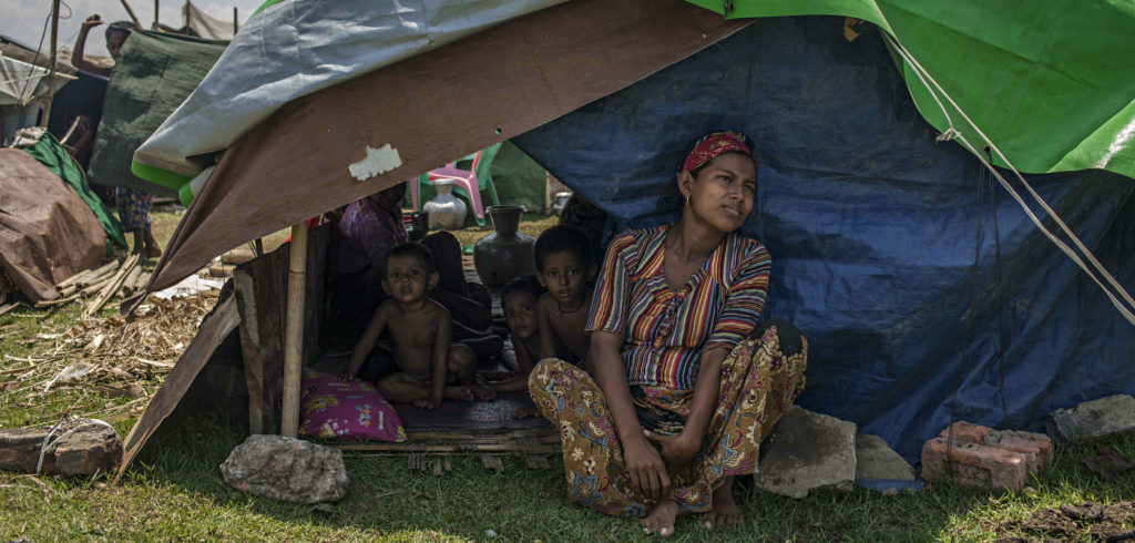 A Rohingya woman sits with her children in their temporary shelter next to the Baw Du Pha internal displacement camp on May 17 in Sittwe, Burma. Photo credit: Lauren DeCicca/Getty Images