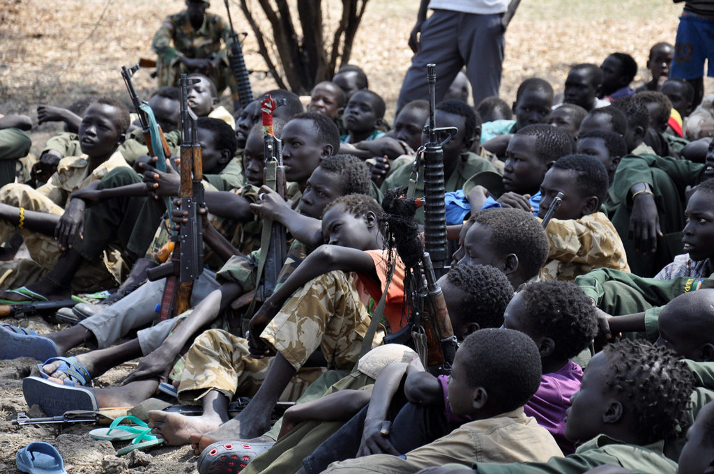Boys sit with their rifles at a ceremony for demobilizing and reintegrating child soldiers in Pibor, South Sudan, on Feb. 10, 2015. Photo: Samir Bol/Anadolu Agency/Getty Images