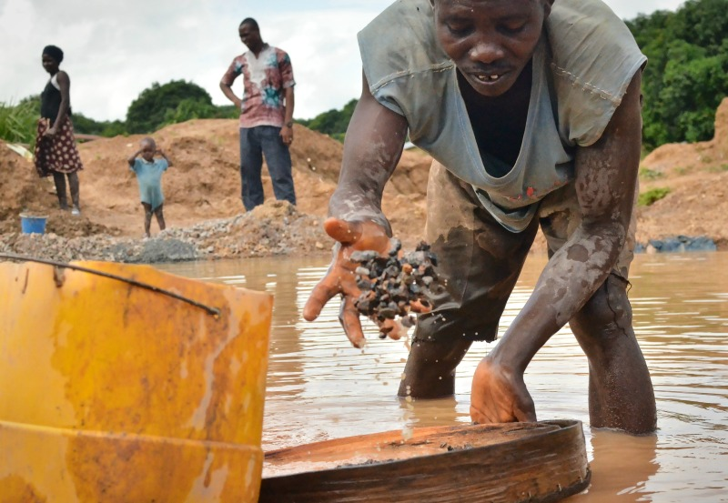 An independent miner panning for diamonds in Sierra Leone. Photo: Cooper Inveen / GroundTruth
