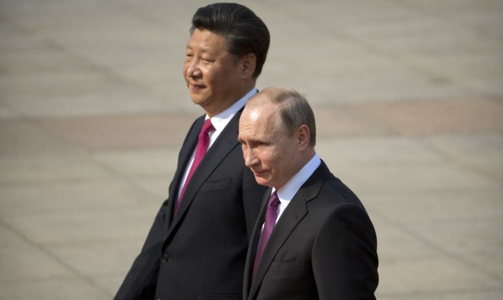 Chinese President Xi Jinping, left, walks with Russian President Vladimir Putin during a welcoming ceremony at the Great Hall of the People in Beijing, Saturday, June 25, 2016. (AP Photo/Mark Schiefelbein)