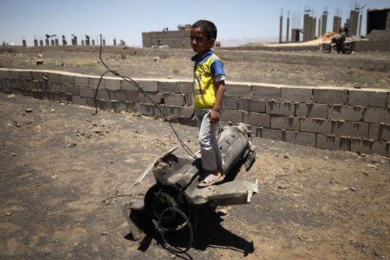 Boy playing on piece of exploded artillery shell which landed near his home, in the village of Al Mahjar, a suburb of Sana'a, Yemen. Photo: UNICEF/Mohamed Hamoud