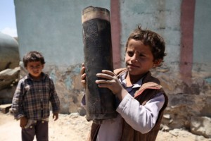 A boy holds a large piece of exploded artillery shell, which landed in the village of Al Mahjar, a suburb of Sana'a, the capital of Yemen. Photo: UNICEF/Mohamed Hamoud