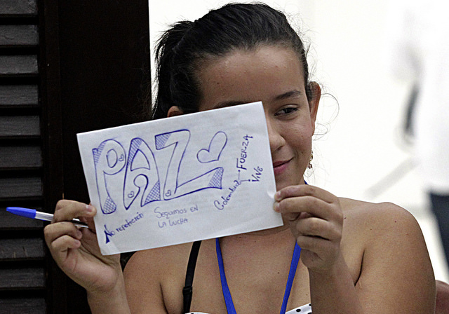 Erika Paola Jaimes, a survivor of Colombia's armed conflict, holds a sign about peace during a trip to Havana to participate in the peace talks between the government and the FARC rebels, which led to a ceasefire signed Jun. 23 in the Cuban capital. Credit: Jorge Luis Baños/IPS