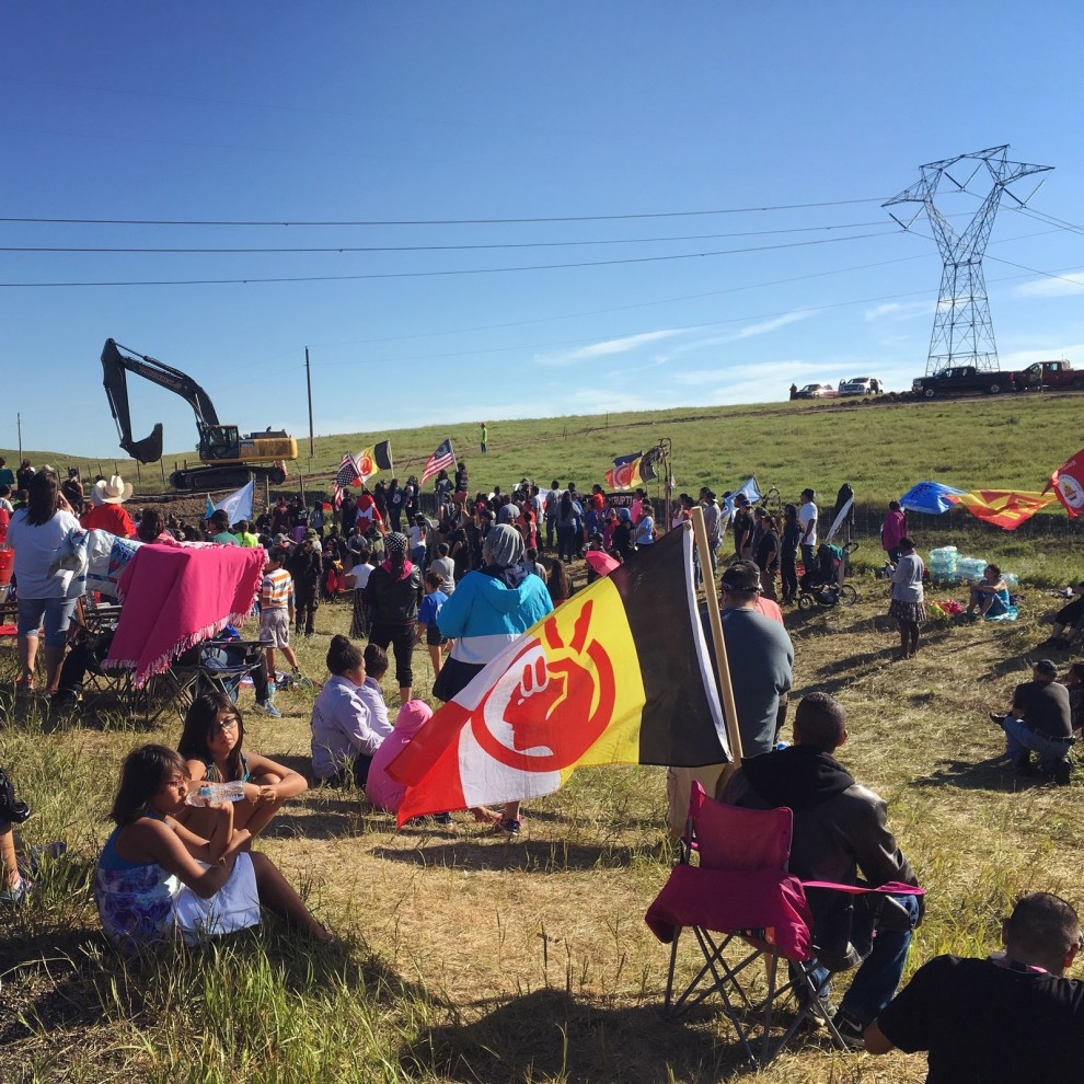 Protesters congregate next to a construction site for the Dakota Access Pipeline on Monday morning, as a crew arrives with machinery and materials to begin cutting a work road into the hillside. The flag in the foreground belongs to the American Indian Movement. Daniella Zalcman