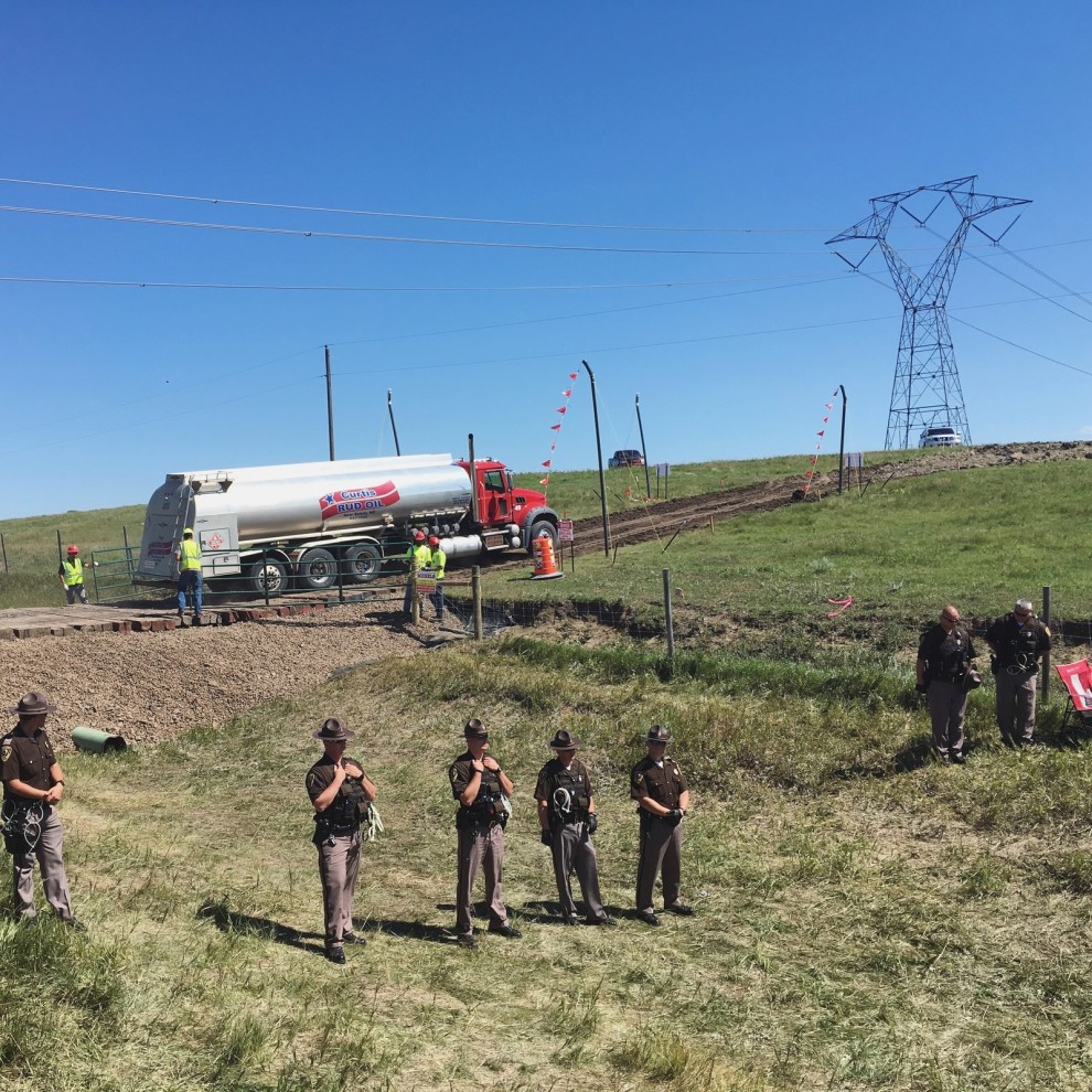 North Dakota state police form a line between the protesters and the entrance to the construction site as a tank truck turns into the property. Daniella Zalcman