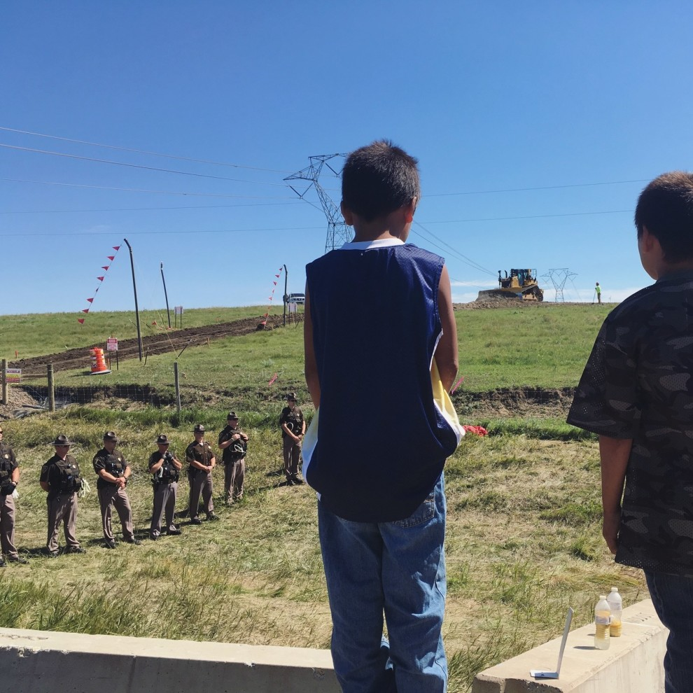 Two young Lakota boys watch as construction machinery drives onto the Dakota Access Pipeline construction site, just over a mile from the banks of the Missouri River. Daniella Zalcman