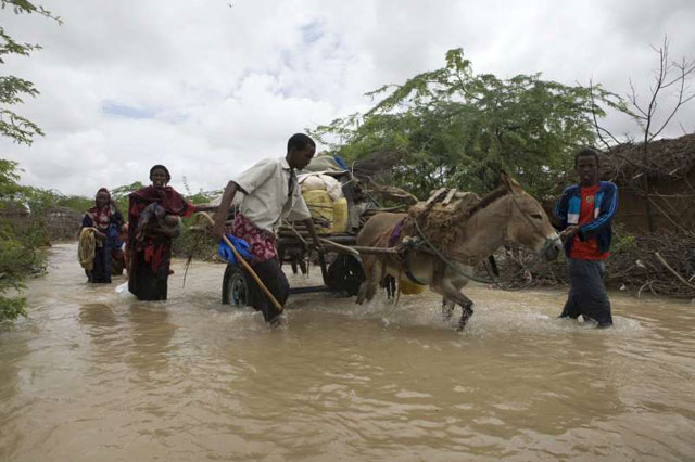Somali refugees flee flooding in Dadaab, Kenya. The Dadaab refugee camps are situated in areas prone to both drought and flooding, making life for the refugees and delivery of assistance by UNHCR challenging. Credit:©UNHCR/B.Bannon