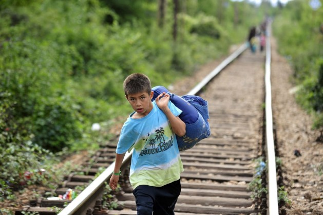 A boy carrying his belongins in a large cloth bag over his shoulder is among people walking on railway tracks to cross from the Former Yugoslav Republic of Macedonia into Serbia. Photo: UNICEF/NYHQ2015-2203/Georgiev