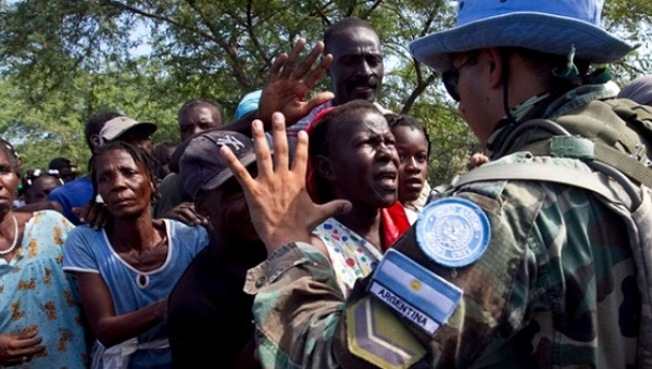 A soldier with the UN Stabilization Mission in Haiti gestures to local residents waiting to receive bottled water. | Photo: Reuters