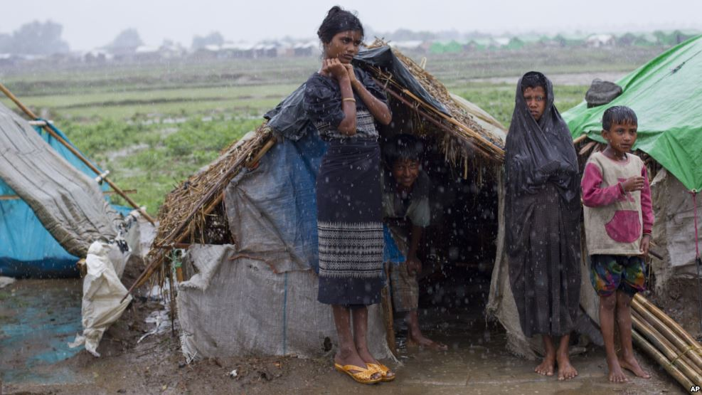 FILE - Internally displaced Rohingya stand outside their makeshift tent in a camp in Sittwe in Myanmar's northwestern Rakhine state in 2013.