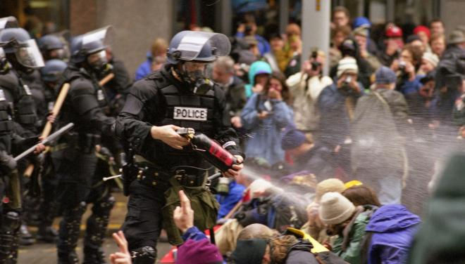 WTO protests in Seattle, November 30, 1999 Pepper spray is applied to the crowd. / Photo credit Steve Kaiser @Wikicommons