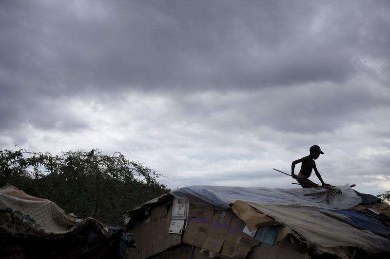 A boy fixes the roof of a makeshift tent at a refugee camp for Haitians returning from the Dominican Republic on the outskirts of Anse-a-Pitres, Haiti, September 6, 2015. © 2015 Reuters
