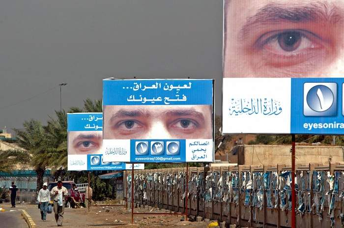 """Iraqis walk under billboards showing posters urging people to report terrorist acts in Baghdad in 2006. The poster shows eyes of a man and a slogan that reads: """"For the sake of Iraq, open your eyes."""" Photo by Sabah Arar/AFP/Getty Images"""