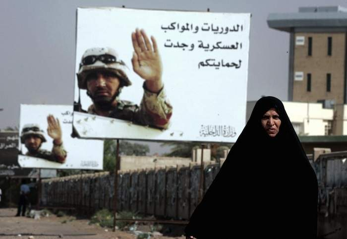 An Iraqi woman walks past billboards reading 'Patrols and military convoys are for your protection' in Baghdad in August 2006. Photo by Karim Sahib/AFP/Getty Images