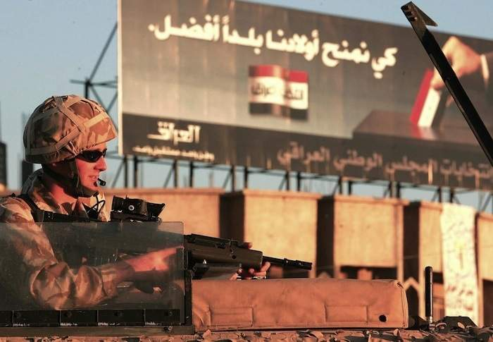 A soldier rides on top of his vehicle past a billboard urging Iraqis to take part in the upcoming elections in Basra in January 2005 Photo by Odd Anderson/AFP/Getty Images