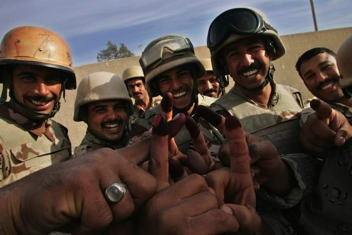 Iraqi soldiers cheer showing ink-stained fingers after casting their vote at a polling station in Baghdad during the 2005 election. Photo by Maurico Lima/AFP/Getty Images