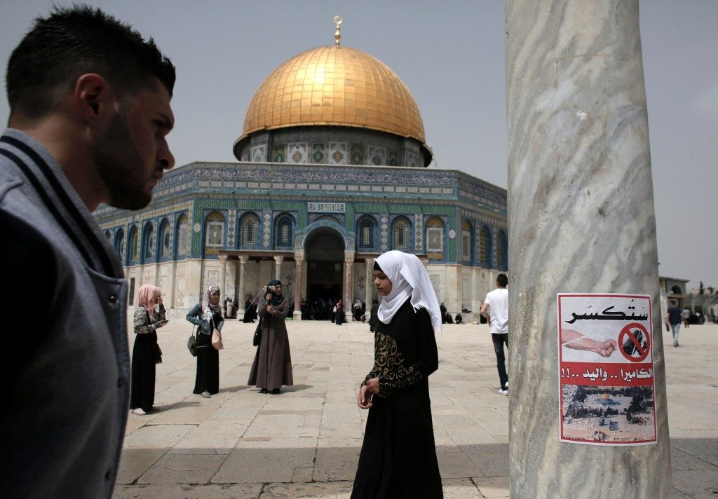 A poster calling for the destruction of CCTV cameras is posted on a column at the Al-Aqsa Mosque compound in Jerusalem in front of the Dome of the Rock, April 8, 2016. Photo: Ahmad Gharabli/AFP/Getty Images