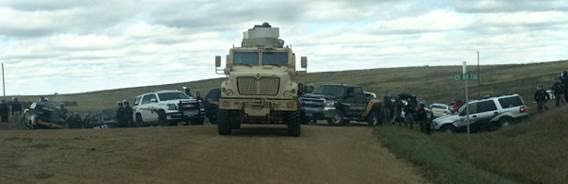 An MRAP (Mine Resistant Armoured Patrol vehicle) and police vehicles block a road in Morton County, North Dakota
