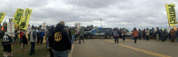 Peaceful water protectors demonstrate in front of a police roadblock preventing them from driving on public roads to pray at one of the Dakota Access construction sites on October 3.