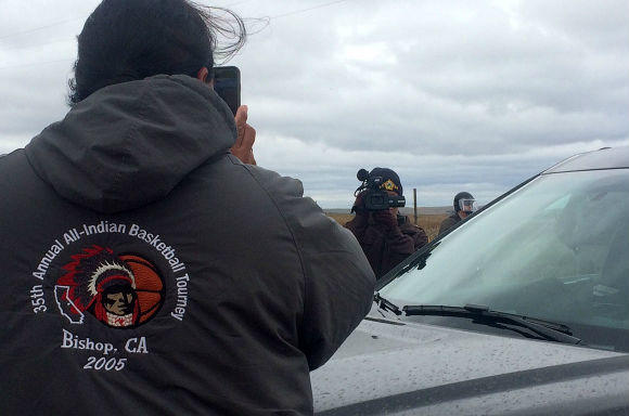 Police and a water protector film each other at a peaceful protest in front of a police roadblock in St. Anthony, North Dakota.